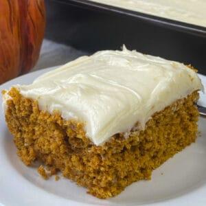 Easy pumpkin carrot cake next to pan full and a pumpkin