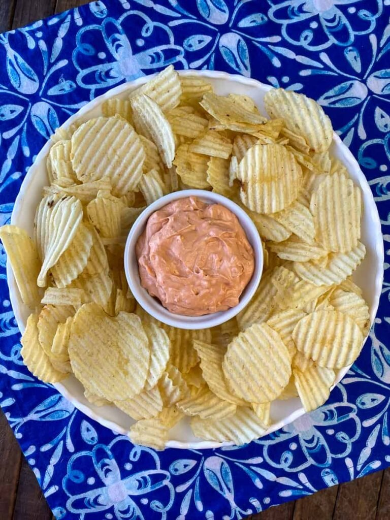 Chips on a tray with homemade dip in the center on a blue napkin