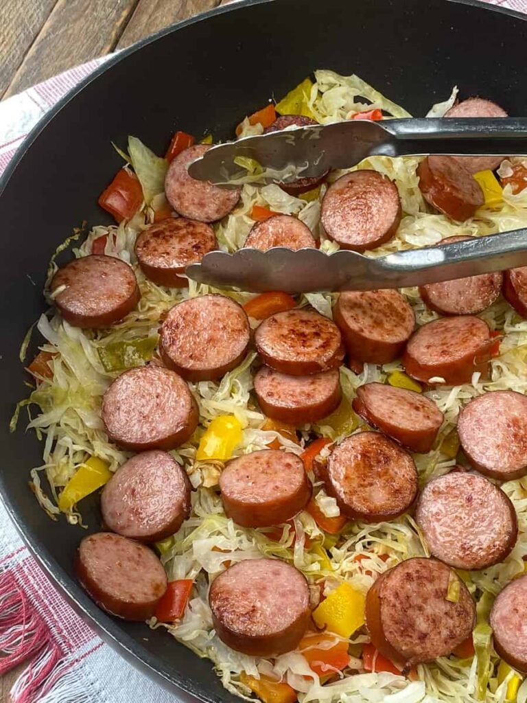 Tongs in cooked Kielbasa and cabbage