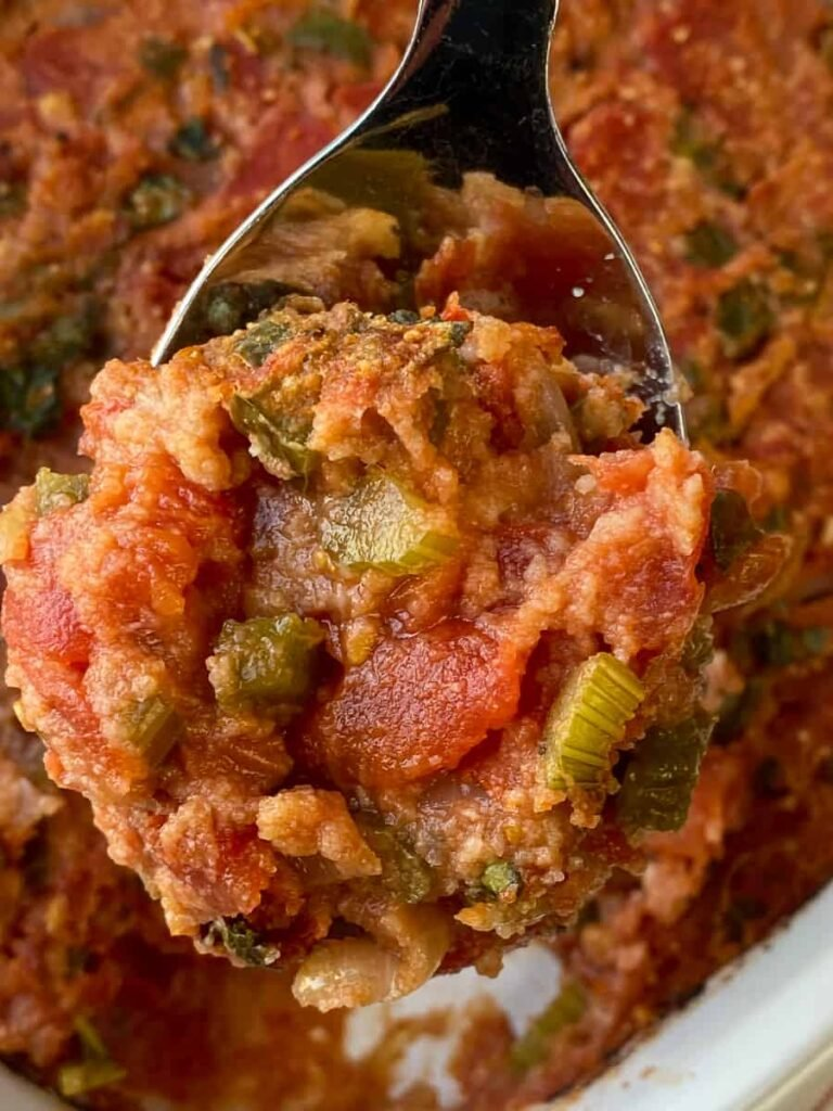 Spoonful of tomato scallop with celery, green peppers and diced canned tomatoes