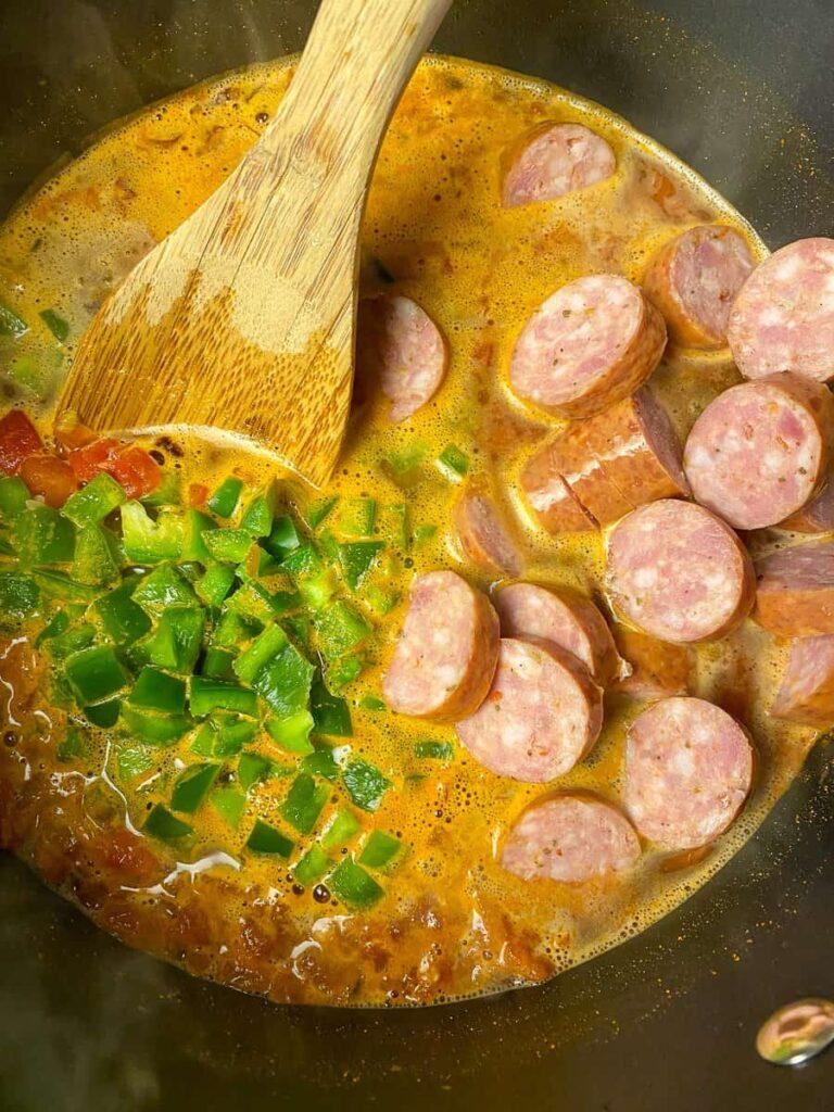 Ingredients to make sausage Jambalaya recipe heating in a pot